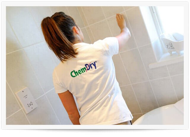 woman cleaning tile and grout